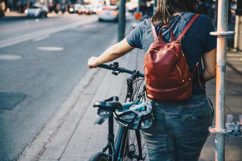 Woman pushing a bike along the sidewalk