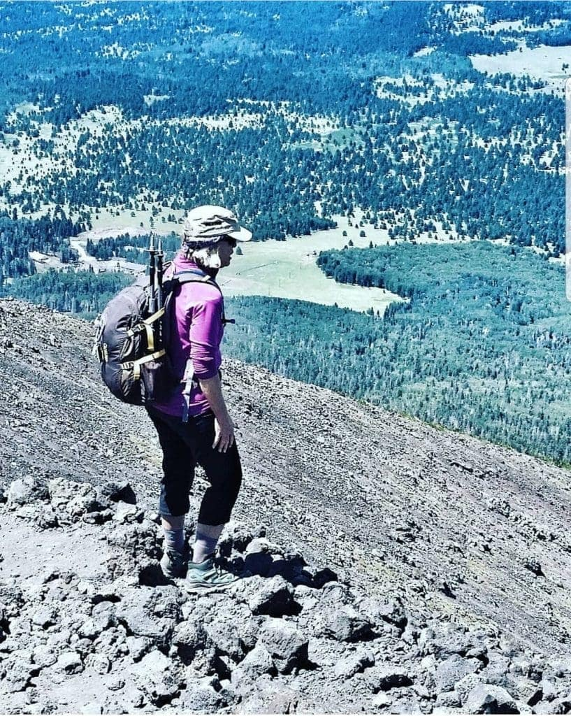 woman stands above treeline on sloping talis. Looks at forests and meadows below
