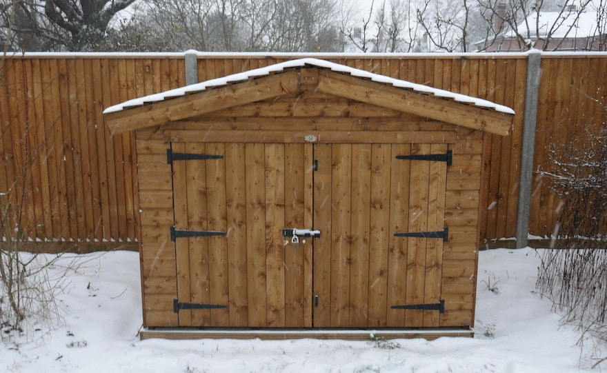 A wooden bike shed in the snow