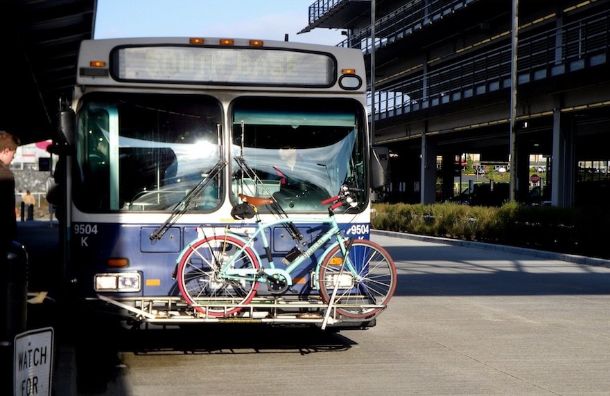 A bicycle loaded onto the bike rack at the front of a transit bus