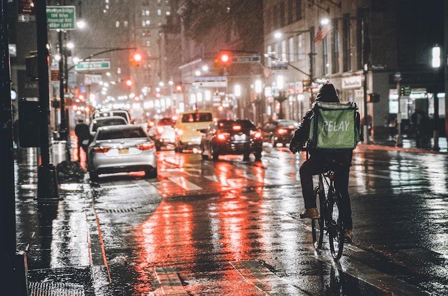 Lone cyclist riding in traffic on a rainy night
