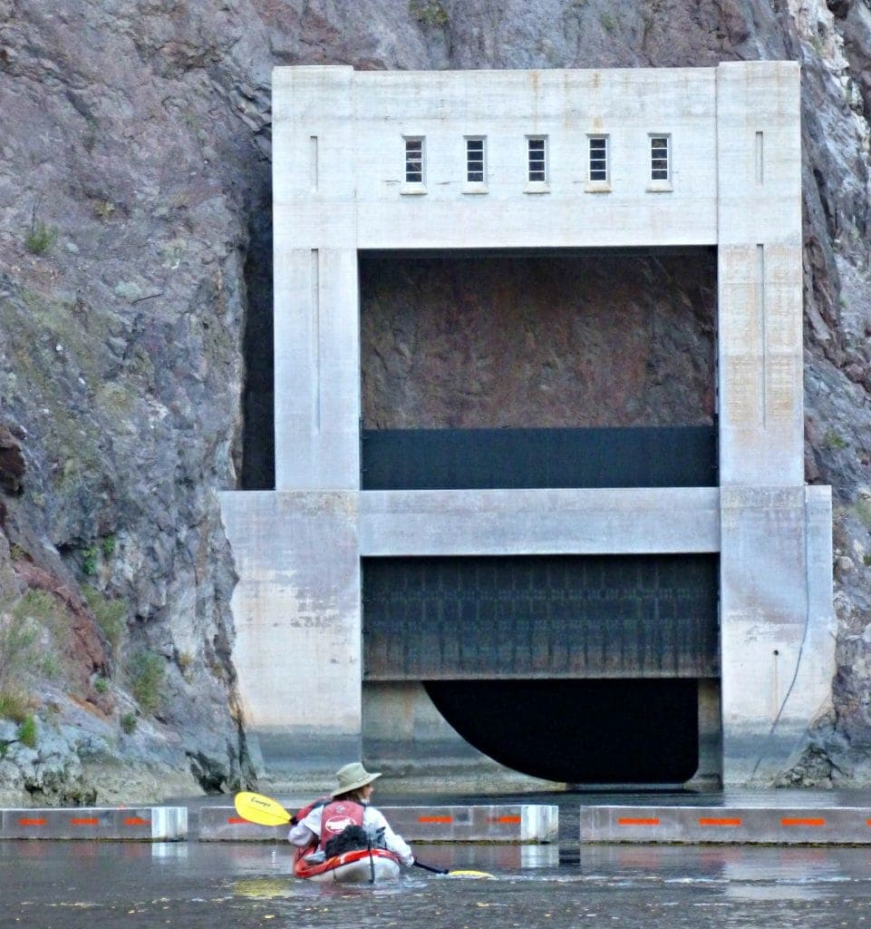 Unstoppable Stacey looks tiny against the dam as she paddles on her Hoover Dam kayak tour