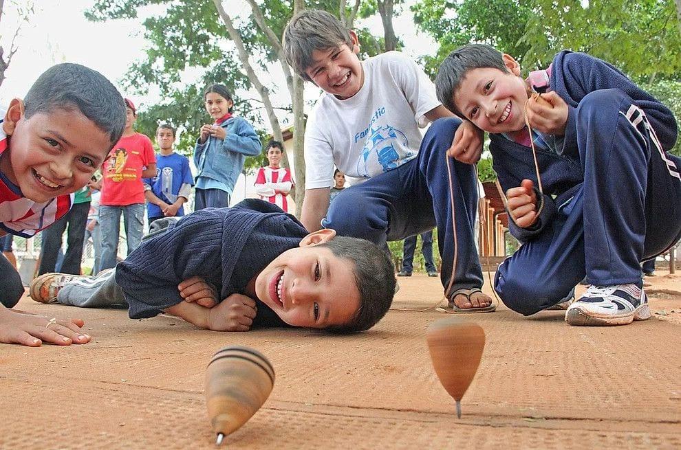 Niños jugando al trompo