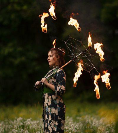Feuershow Artistin zeigt brennenden Regenschirm um alten Japan Stil