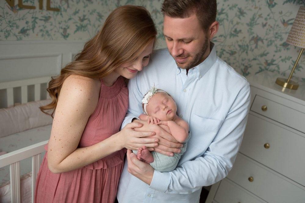 mom and dad in nursery with newborn in san antonio, texas