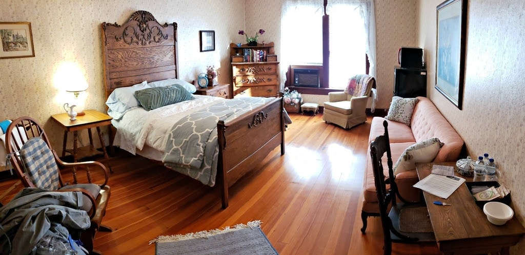 interior of guestroom decorated in Victorian antique furniture, wood floors, sunny window