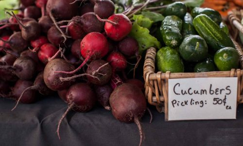 A close-up photo of a bunch of beets and pickling cucumbers in a basket.