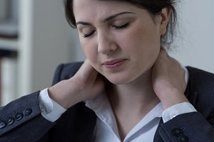 Female white-collar worker having neck pain, close-up