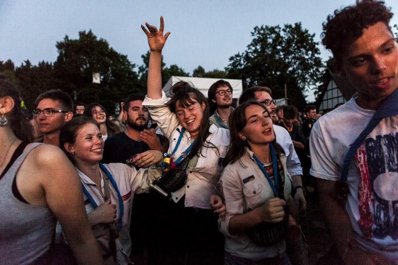 Junge Pfadfinder*innen tanzen ausgelassen zur Musik auf einem selbstorganisierten Bandfestival./ Young Boy and Girl Scouts dance exuberantly to music at a self-organised band festival.