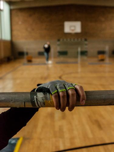 Die Hand eines Spielers am Gestänge des Tors. Die Spieler halten sich am Gestänge fest um sich zu orientieren.
