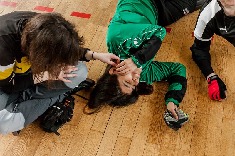 Während einer Trainingspause liegen die Torball-Spielerinnen auf dem Hallenboden und necken sich gegenseitig.
