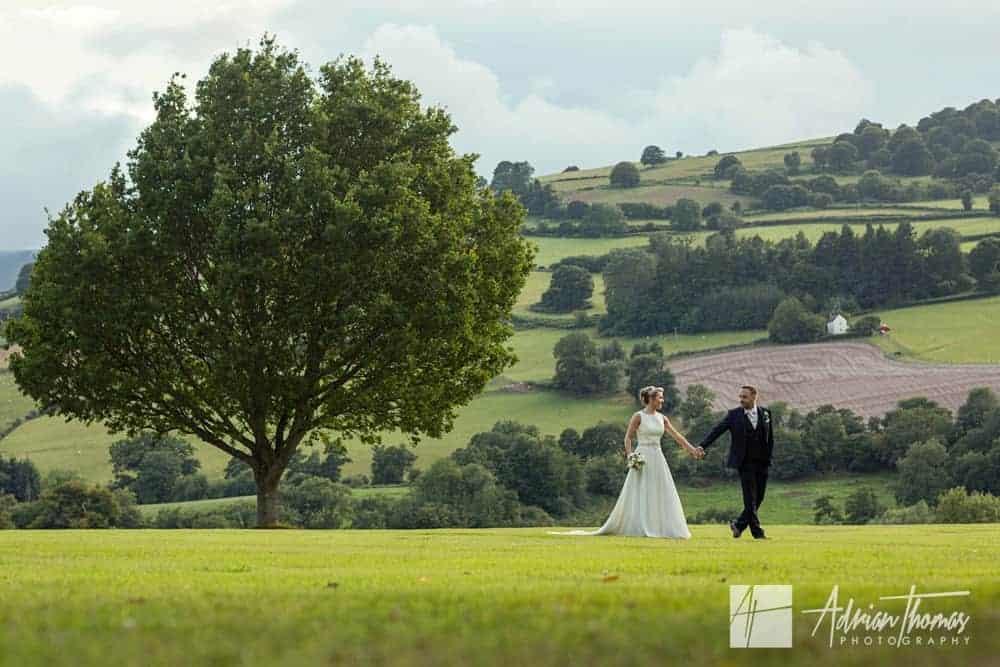 Bride and groom walking at Buckand Hall wedding reception.