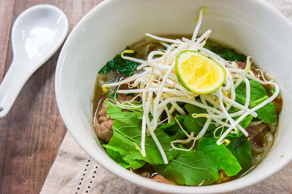 A plate of condiments such as basil, cilantro, bean sprouts and lime allow you to customize your own bowl of pho.