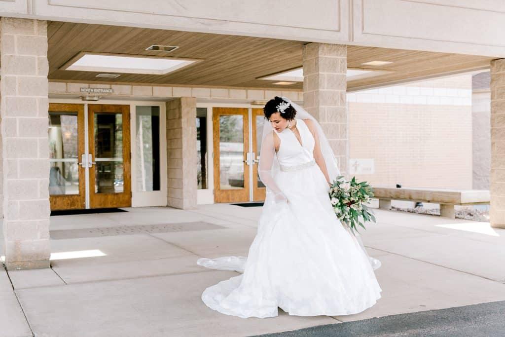 bride standing in front of the door holding wedding flowers