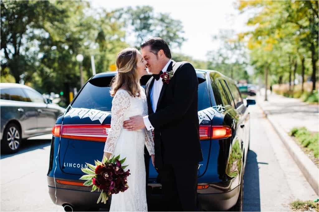 bride and groom kissing in formt of the limo