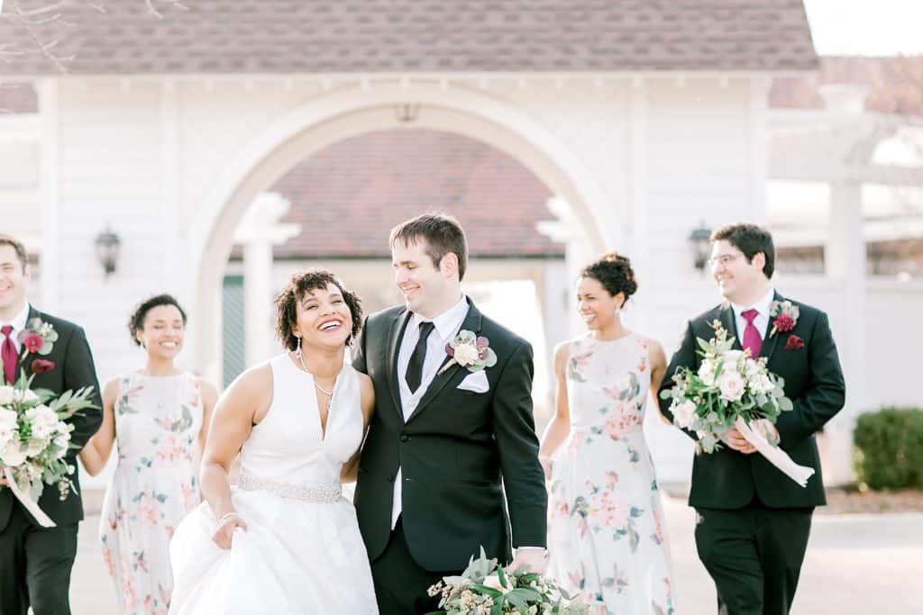 bridal party walking and laughing in front of danada house in Naperville IL