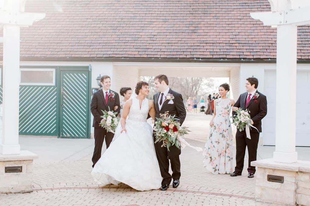 bridal party walking and laughing in front of the Chicago wedding venue danada house