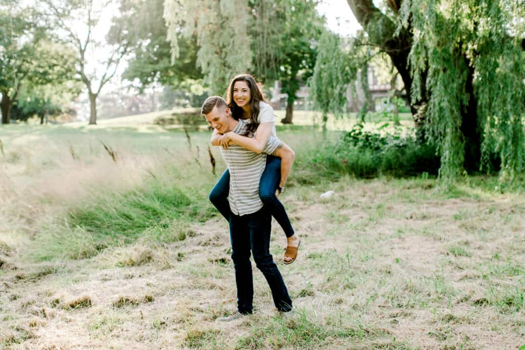 guy holding girl on his back during an engagement session in mayslake peabody estate