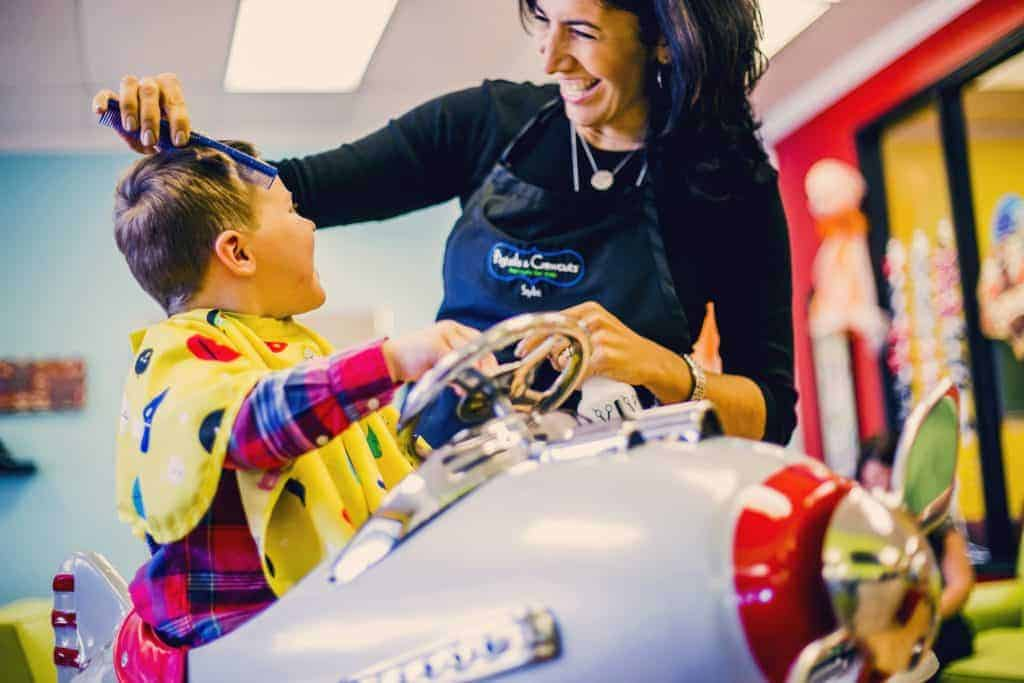 Stylist and client interacting at Pigtails & Crewcuts children's haircut franchise