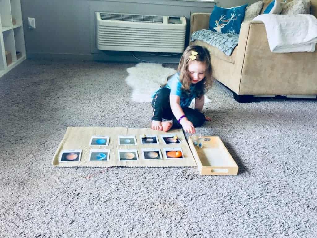 Montessori child matching planet manipulatives to planet cards