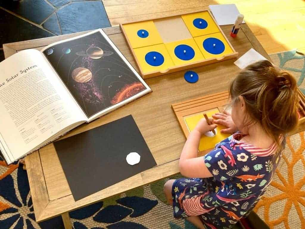 Montessori First Great Lesson Follow-up work:  child tracing Geometry Cabinet Circles Drawer and Planetarium book open to The Solar System