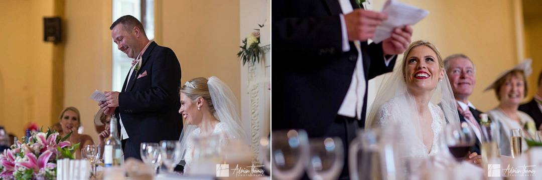 Bride smiling at groom while he does his wedding reception speech.