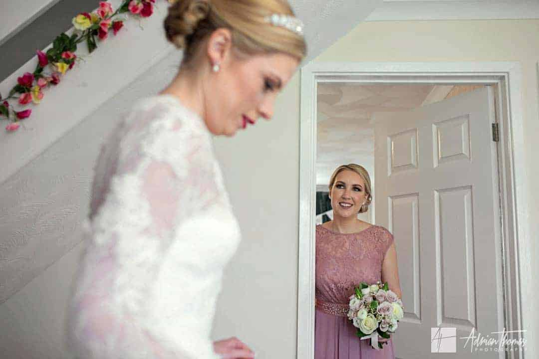 Bridesmaid sees bride in her dress for the first time.