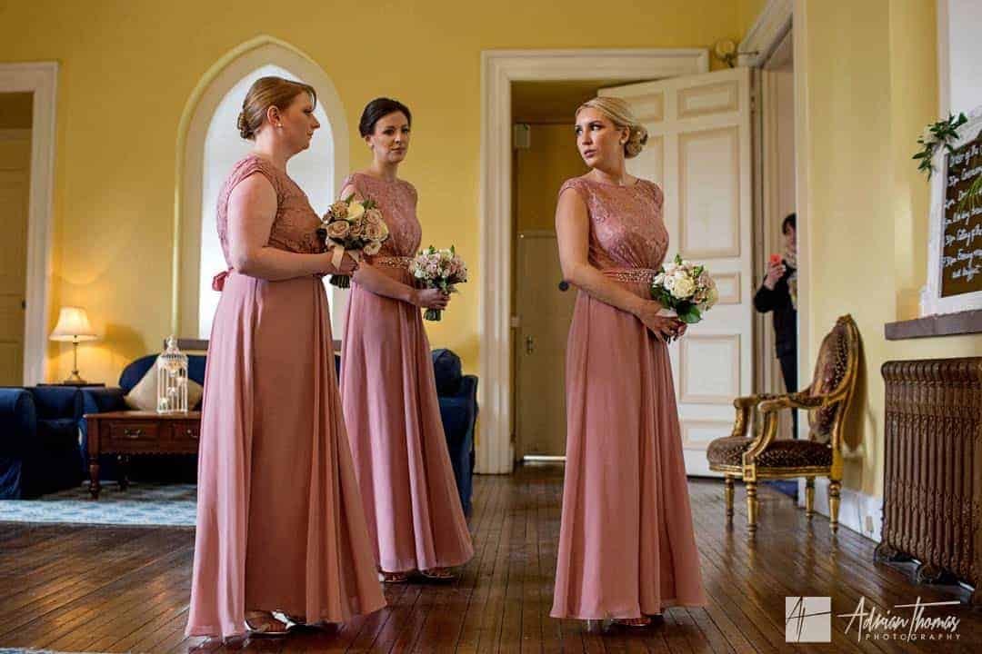 Bridesmaids waiting to enter the ceremony room at a Clearwell Castle wedding.