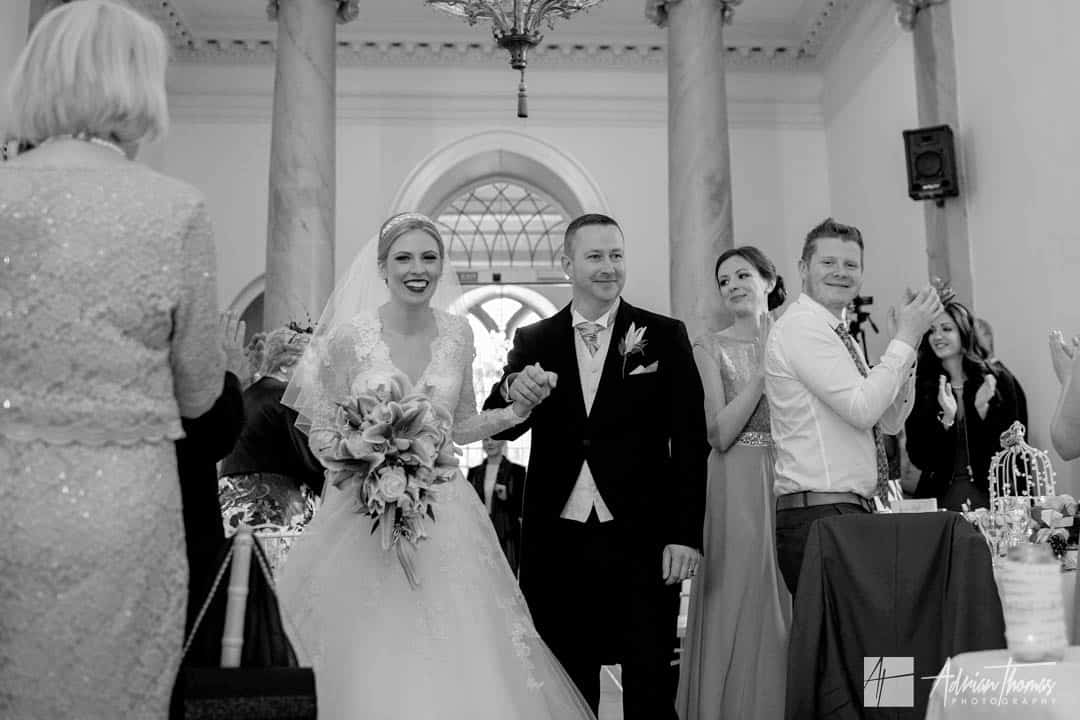 Brdie and groom enter wedding reception room with guests clapping.