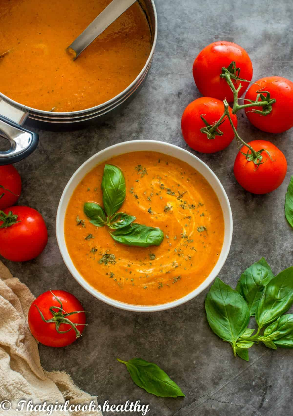 soup in a white bowl with tomatoes surrounding it