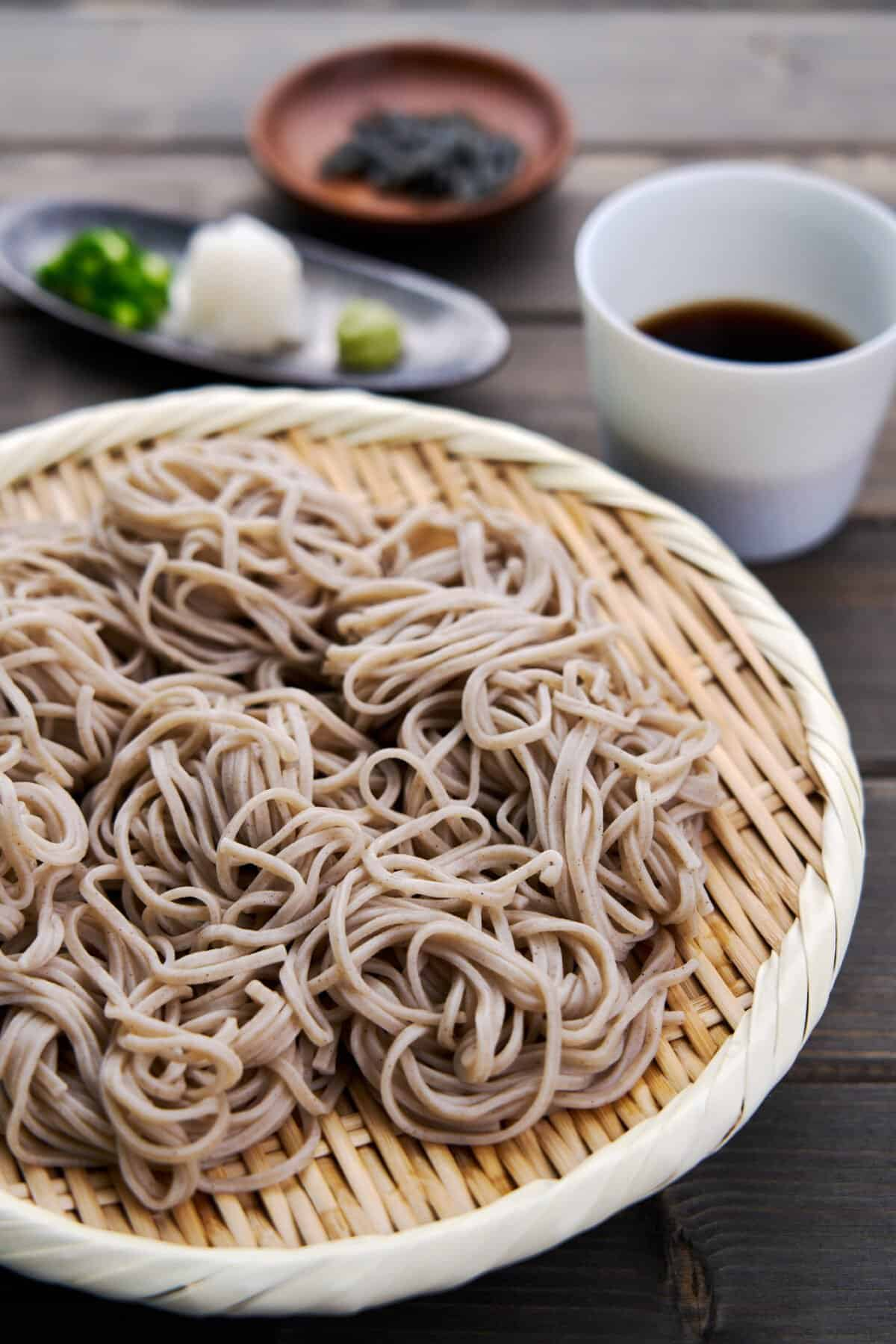 Chilled soba noodles, known as Zaru Soba in Japan is a refreshing summertime meal served with a savory dipping sauce and condiments such as wasabi, scallions, nori and grated daikon.