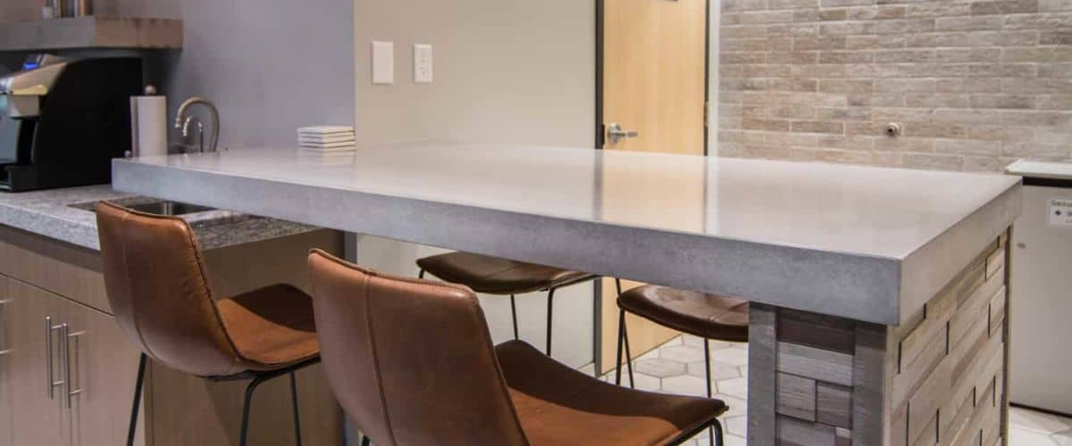 Concrete Countertops and Brown Leather Chairs