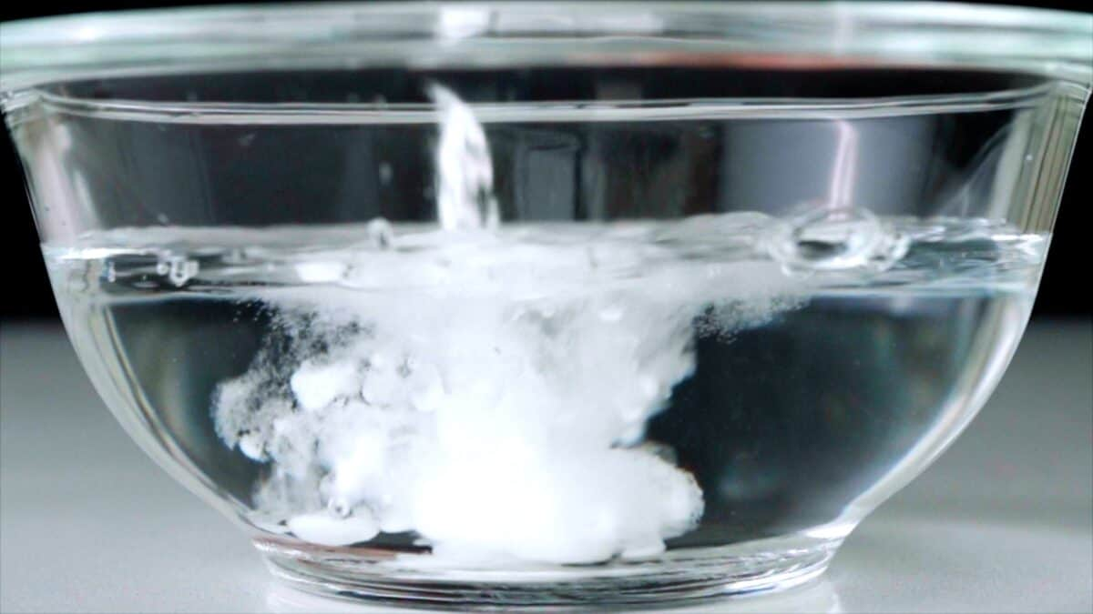 Baking soda going into a glass bowl filled with water to make a brine for shrimp.