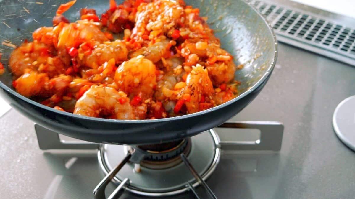 Tossing Cajun shrimp in a frying pan.