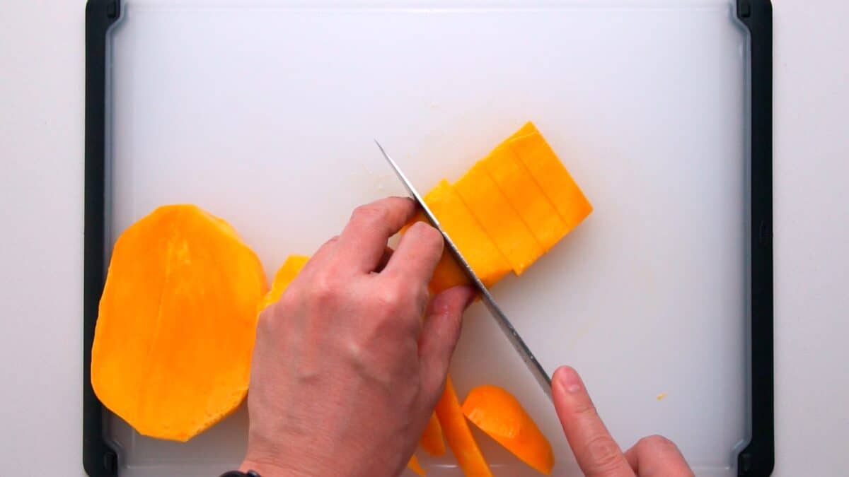 Slicing mango into batons for fruit sandwiches.