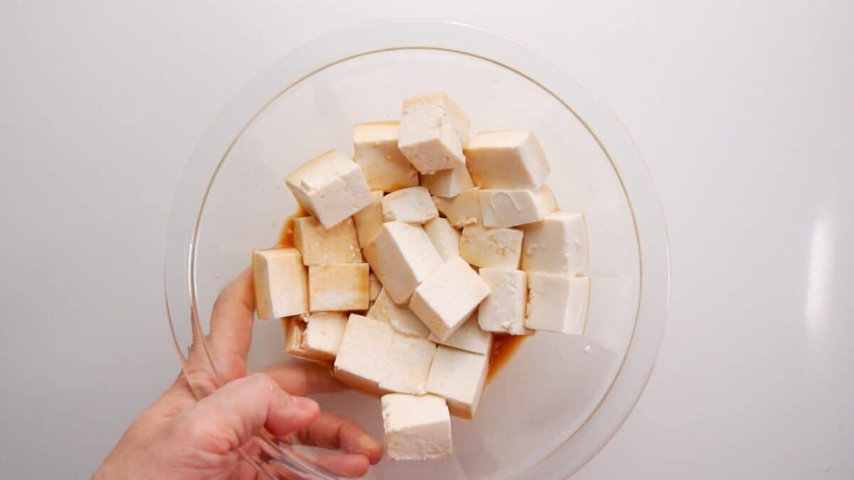 Marinating tofu in glass bowl for Kung Pao Tofu.