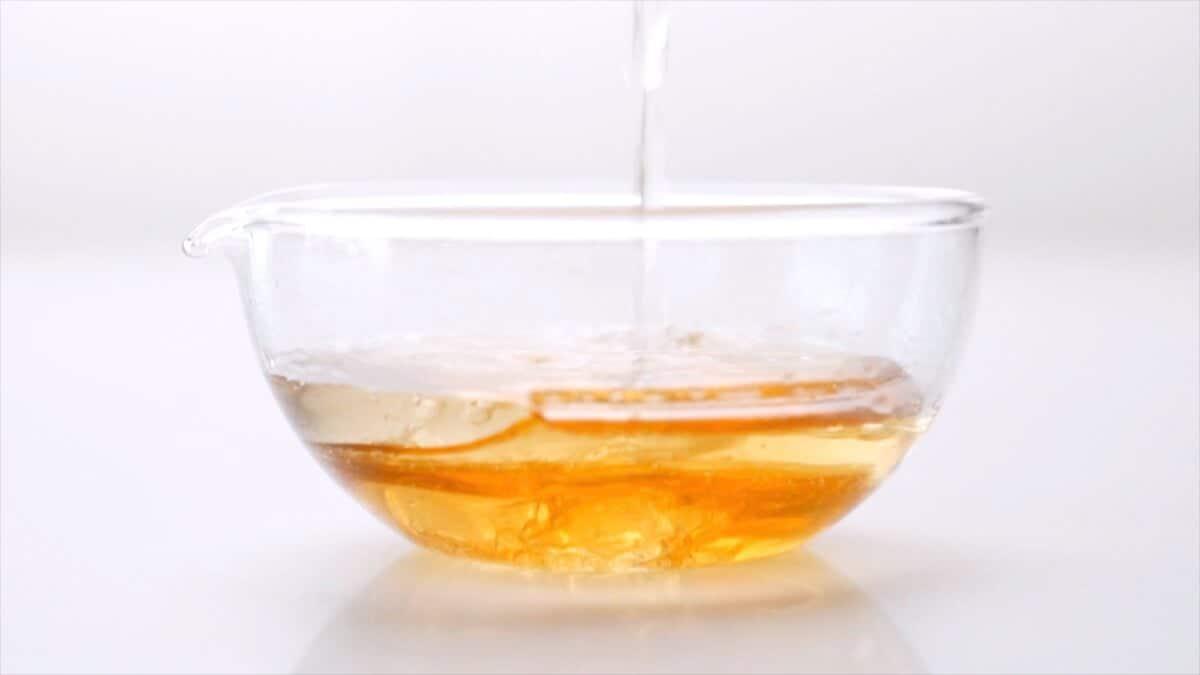 Mixing white wine and honey to make honey garlic sauce.