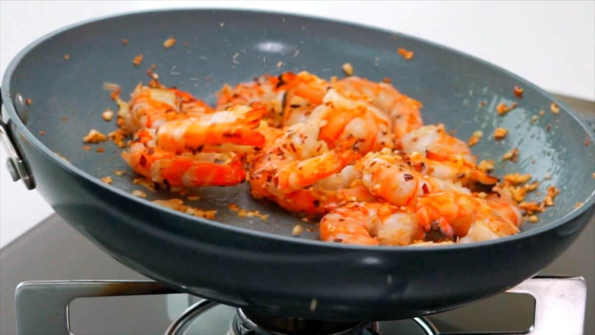 Tossing shrimp and garlic in a plan.