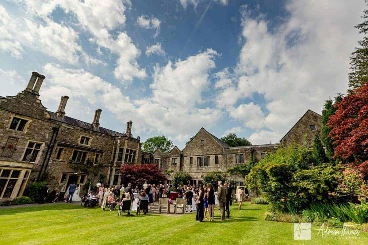 Guest mingle at Miskin Manor wedding venue gardens.