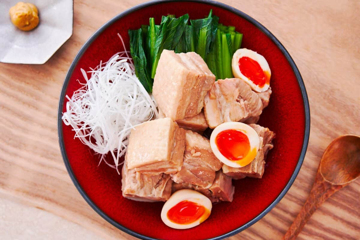 Kakuni is a Japanese classic made by braising pork belly in aromatics until fall-apart tender. The braising liquid can then be used to make marinated ramen eggs.