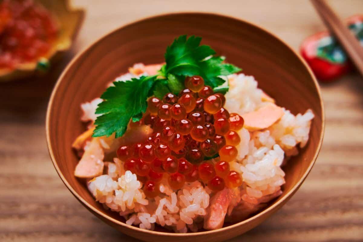 Salmon Takikomi Gohan topped with mitsuba and ikura. A popular fall meal in Japan.