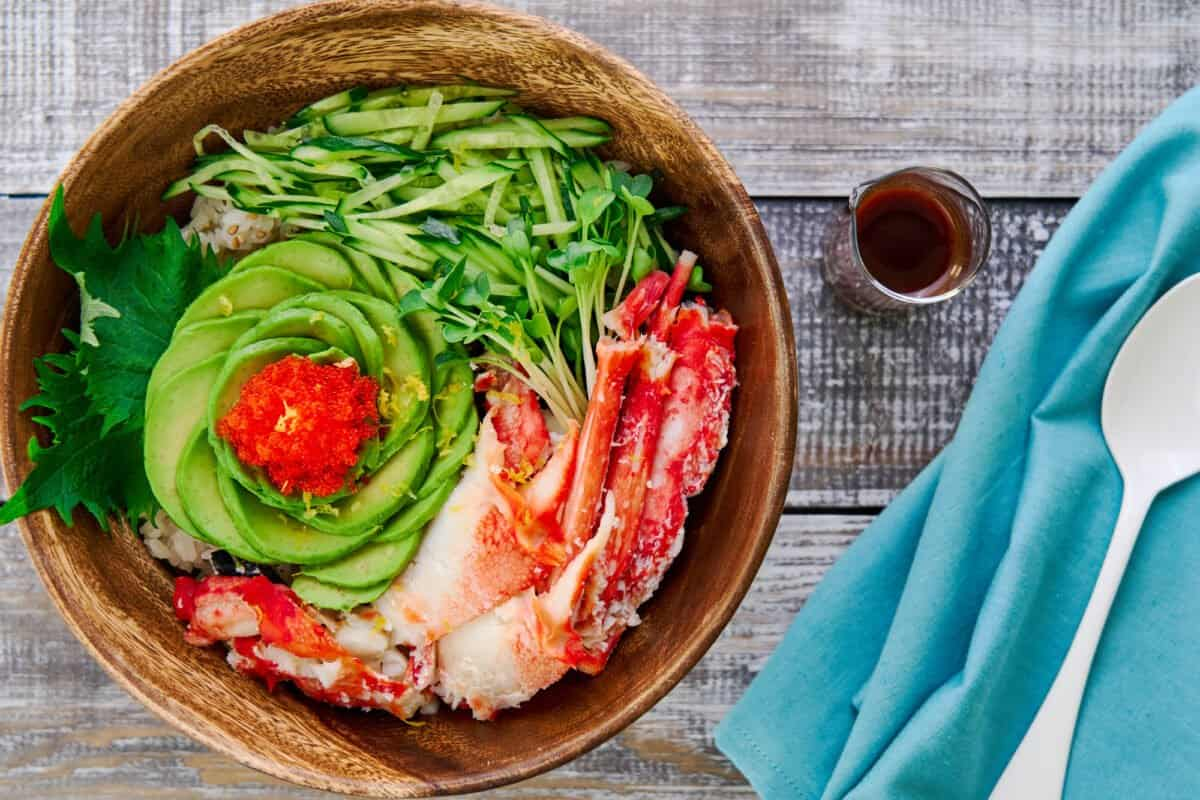 This California roll in a bowl has savory crab, creamy avocado, crunchy tobiko, and crispy cucumbers on a bed of nori and sushi rice.
