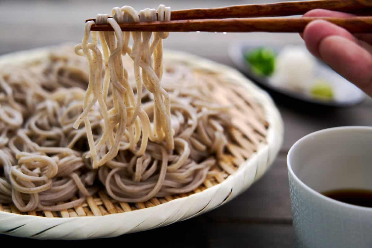 Chilled soba noodles get lifted off a zaru with chopsticks for dipping into soba sauce.