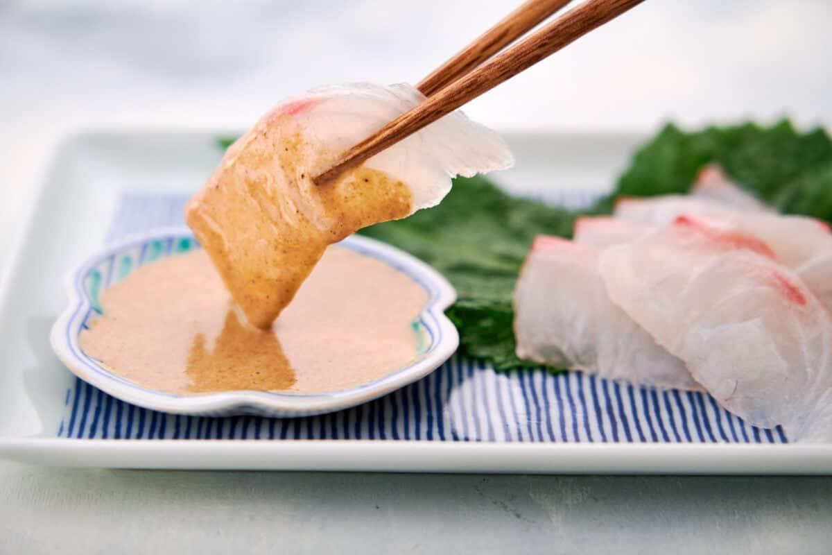 Tai (Sea Bream) sashimi being dipped in Japanese sesame sauce.