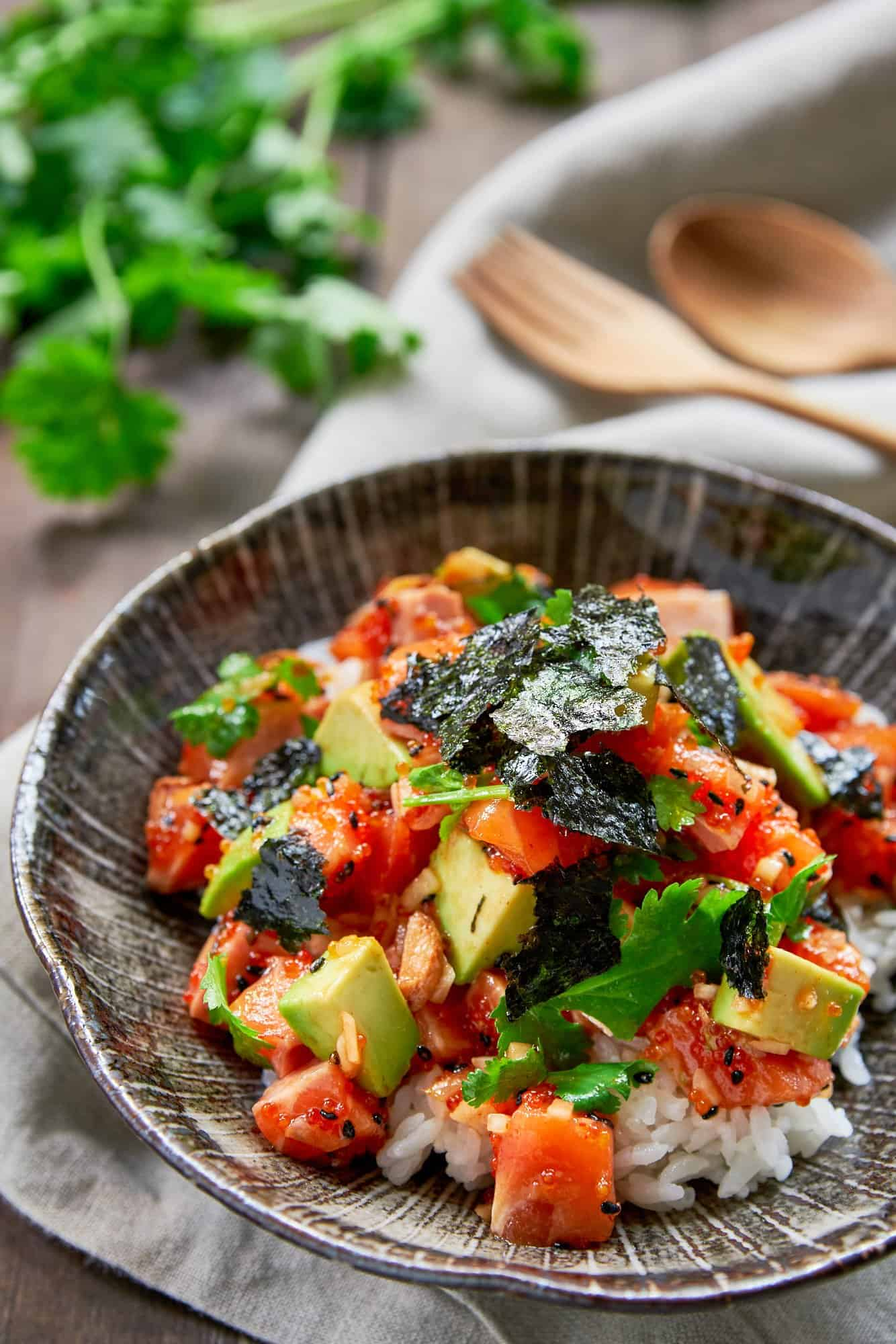 The best Spicy Salmon Poke recipe. With rich salmon, creamy avocado, crunchy tobiko, sweet onions and fresh cilantro seasoned with a sriracha sesame sauce and served over a bowl of hot rice.