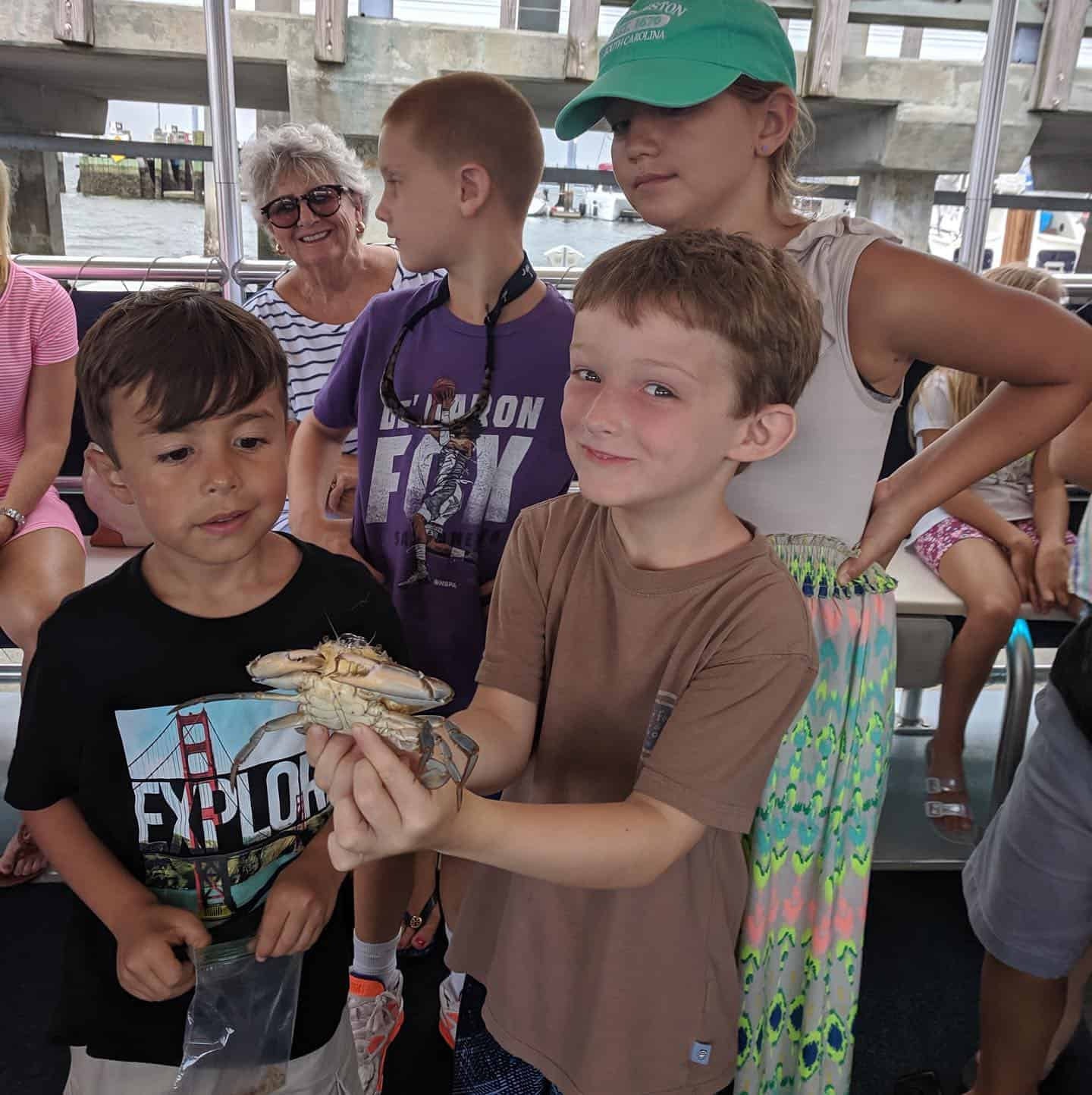 Young kid holding live crab. Nature boat tours Charleston