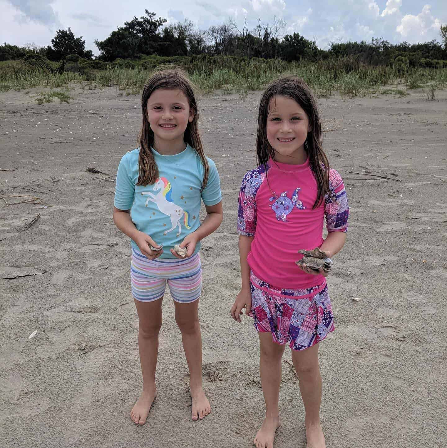 Two young girls pictured on beach with the shells they have collected in their hands. Best boat tours in Charleston, SC