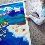 child playing with montessori air, land, and water mat