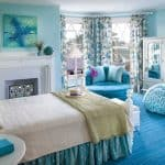 a blue beach-themed bedroom with blue-white floral-patterned curtains