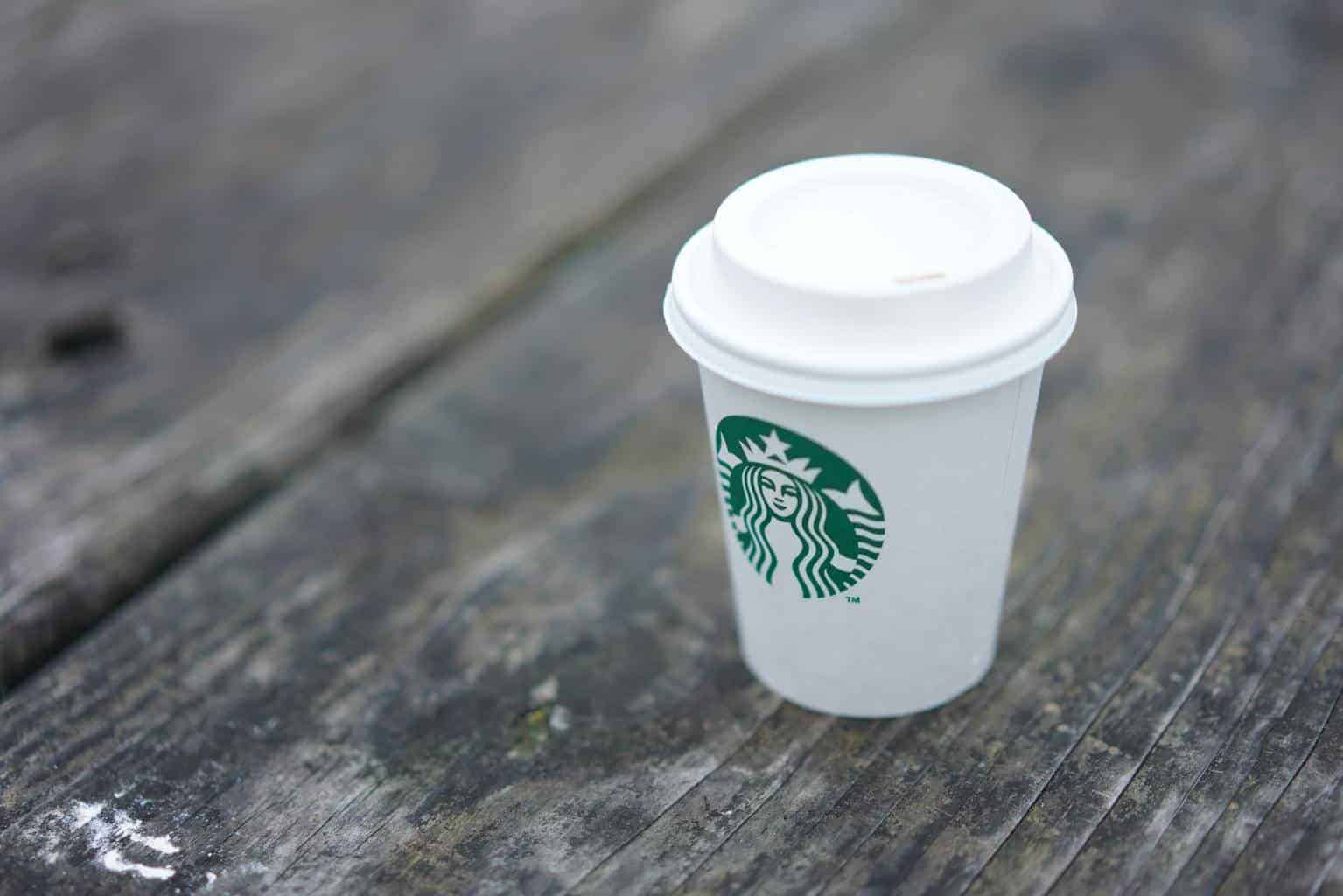 Short Starbucks cup on a wooden plank surface
